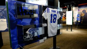 Game-worn jerseys hang in plastic cases, including one worn by the most famous Indianapolis Colt of all.