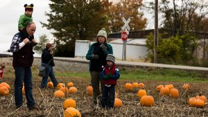 Scott and Rachel Gottshall, along with Emory (on Scott's shoulders) and Amos, mull over pumpkin options.