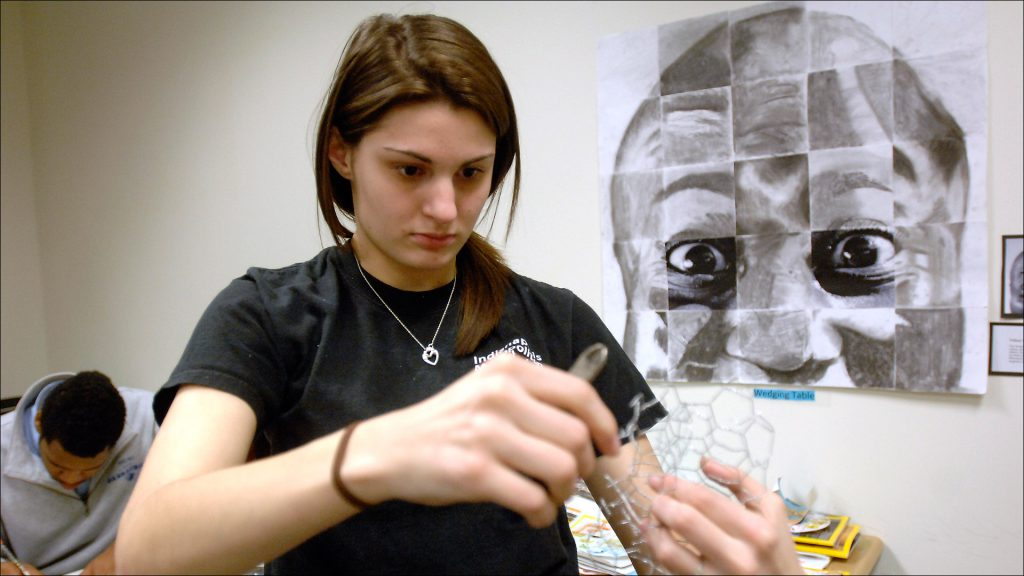 Student Stefani Amsden cuts wire for an art project. The school features unusual subject combinations, such as geometry-art.