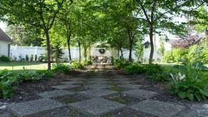 The backyard once was a junk yard but it has been transformed into a formal garden with tree-lined pathways.