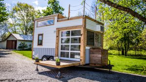 The tiny house includes a garage door that leads onto the deck to make home feel more open. A hatch in the loft leads to a roof-top deck.