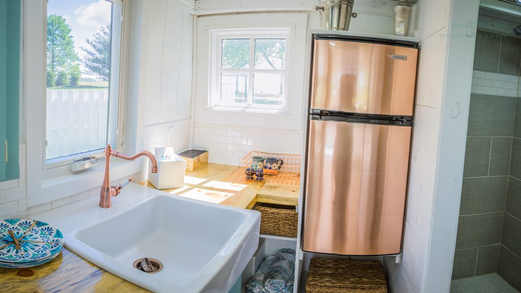 The kitchen has a surprising amount of counter space and a larger sink. An apartment-size refrigerator and two-burner stove round out the space.