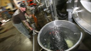 Sun King's Adrian Ball cleans out lines and brewing tanks with fresh water and a cleaning agent.